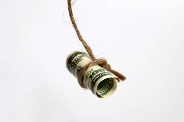 A hundred dollar bill hanging from a rope.