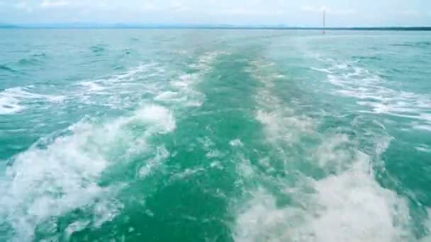 Proud vody a kouř z motoru po rybářské lodi u pobřeží