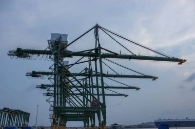 Industrial crane formation in export import and commercial port in Jakarta, gantry cranes ready for loading and discharging cargo from vessels