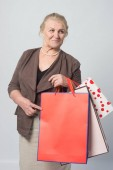 Fényképek egy öregasszony gazdaság bevásárló táskák