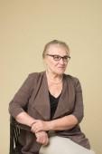Fényképek Portréja egy öregasszony, szemüveg egy bézs háttérrel