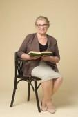 Fényképek portréja egy öregasszony, szemüveg egy fonott szék, egy bézs háttérrel