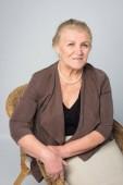 Fényképek portréja egy régi asszony fehér alapon fonott szék