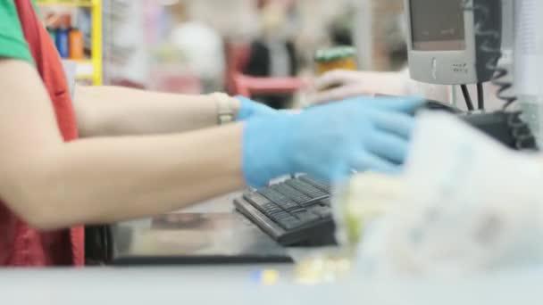 A szupermarketben dolgozó munkás gumikesztyűs termékeket néz meg egy árucikk szalagon. Coronavirus fertőzés elleni védelem. Karantén előkészítése.