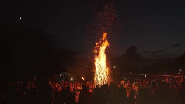 lidé stojí kolem velkého táboráku na festivalu