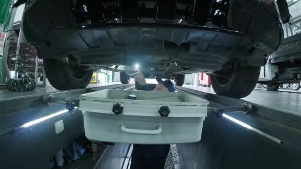 Mechanic in the pit checks bottom of car