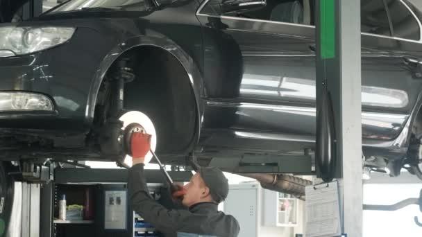 automechanik nahrazující auto kolo brzdy boty zvednutý automobil na opravárenských čerpacích stanicích