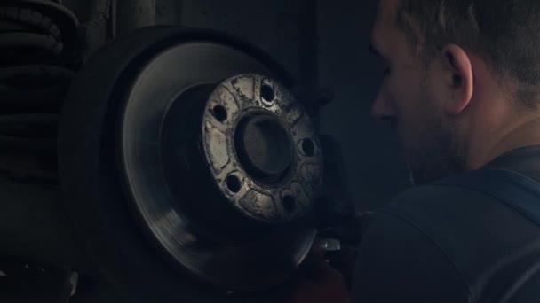 Automechanik nahrazující brzdové boty zdviženého automobilu na opravárenských čerpacích stanicích