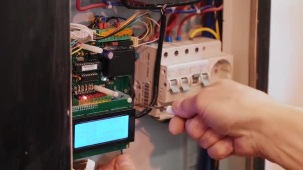 Elektrikáři pracují na elektrickém proudu v ovládacím panelu. Práce inženýra elektrotechniky