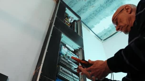 Elektrikáři testují proud v ovládacím panelu. Elektrikář práce tester měření napětí a proudu elektrického vedení v elektrickém skříni řízení.