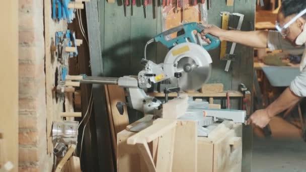 Tesařská dílna - profesionální nástroj na pracovišti - ořezávátko. Pracovník ořezává dřevo na ořezávacím stroji