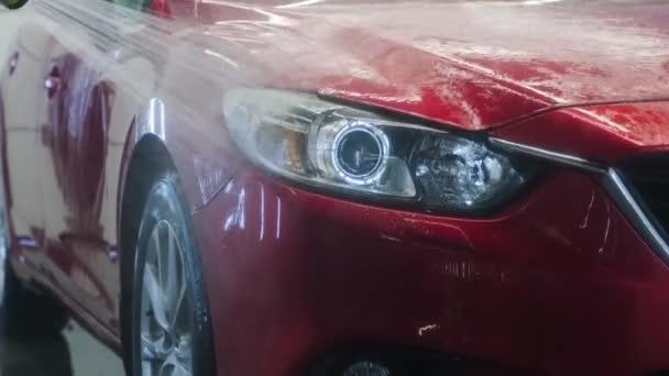 Mytí aut pěnou a vodou s vysokým tlakem. Červené auto