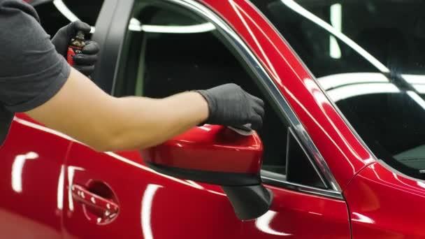 Autoservice-Mitarbeiter trägt Nano-Beschichtung auf ein Detail im Auto auf.