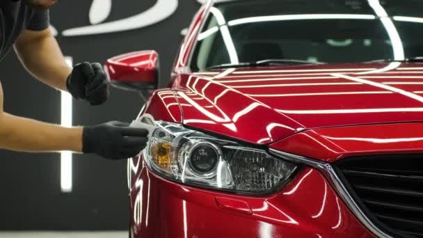 Autószerelő, aki nano bevonatot alkalmaz az autó részleteiben.