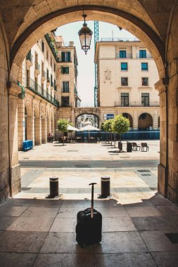 Spain Tourism: Street view and Luggage under an Arch Gate in Alilcante
