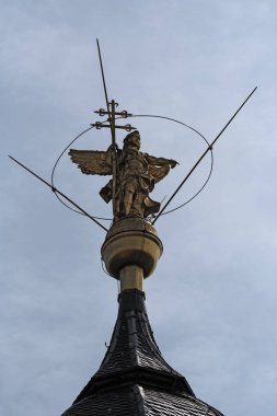 copper statue of the archangel gabriel on the top of the church of st. marcellinus and st. peter, seligenstadt, hesse, germany