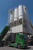 Zementwerk mit Silos und grünen LKW-Mischsilo-Konstruktionen