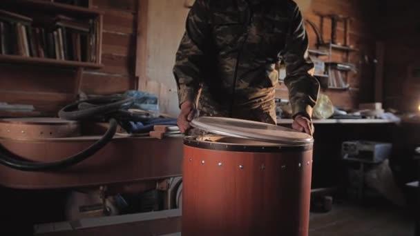 Arbeit sammelt ethnische Trommeln. Es installiert sich auf dem Kunststoff. Montage von Instrumenten.