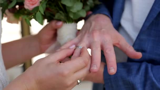 A girl puts a ring on her boyfriends hand. Two newlyweds. Close up