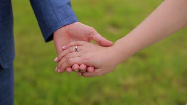 Chlápek drží svou milovanou za ruku a přejíždí jí prstem po ruce. Zavřít. Šťastní spolu.