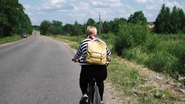 A woman takes a bike ride on a country road. A car is coming towards us. Slow-motion images. Cinematic slowdown