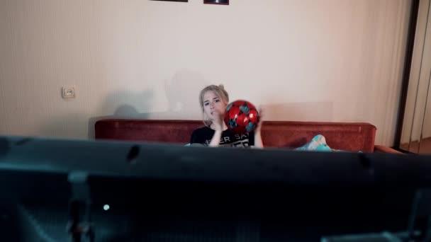 Das Mädchen sieht Fußball auf dem Sofa sitzen und wirft den Ball in die Hände. Sie trinkt Bier. Emotionale Betrachtung