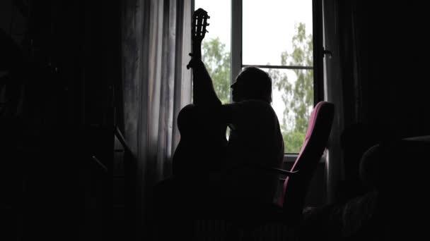 Chlápek sedí na židli před oknem a hraje na kytaru. Smutná nálada. Krásná silueta