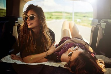 Two girls lying down in the trunk and resting frome driving car.