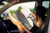 GIrl looking at map with legs on the car window.