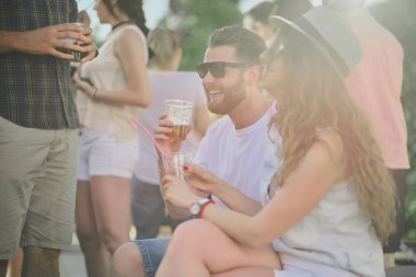 Couple sitting and drinking alcohol at outdoor party