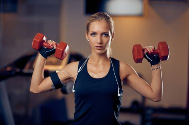 Beautiful blonde girl lifting dumbbells while standing in gym. Healthy lifestyle concept.