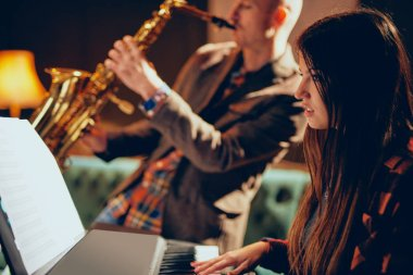 Young Caucasian woman with long brown hair playing electric piano and in background saxophonist playing his instrument. Home studio interior.
