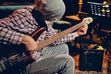 Young Caucasian man with hat on head playing bass guitar while sitting in home studio.