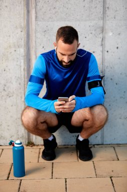 Young bearded man crouching and using smart phone. Next to him bottle with water. In background wall. Healthy lifestyle concept.
