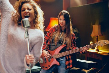 Two women practicing for the gig. Woman with curly hair holding microphone and singing while other one playing bass guitar. Home studio interior.