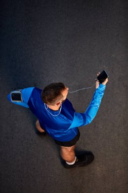 Top view of runner standing on the street and using smartphone. Healthy lifestyle concept.
