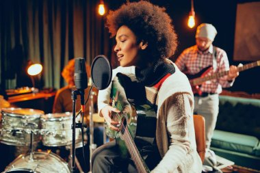 Mixed race woman singing and playing guitar while sitting on chair with legs crossed. In background drummer and bass guitarist.
