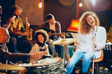 Jazz band preparing for the gig. In foreground woman singing while the rest of the band playing bass guitar, clavier and acoustic guitar. Home music studio interior.