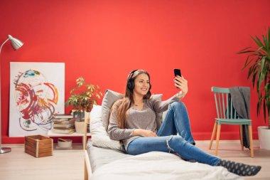 Rahat ve haedphones ile yatak yatak odasında oturma ve selfie alarak kulaklara gülümseyen beyaz esmer güzel giyinmiş.