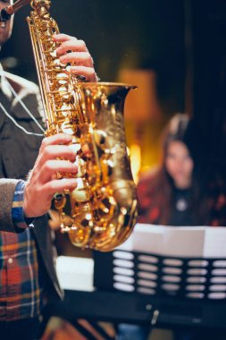 Man playing saxophone in home studio while young talented woman playing clavier.