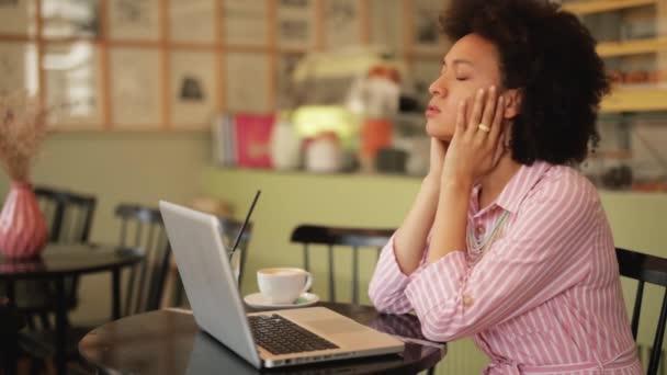 Nyomott vegyes verseny nő ül a kávézóban, és tartja a fejét a kezében. Előtte van laptop.