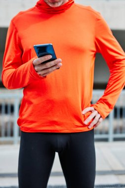 Runner standing in urban exterior and using smart phone to check out how many miles he ran.