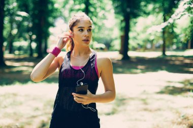 Young attractive sportswoman putting earphones in ears and preparing for running in nature.