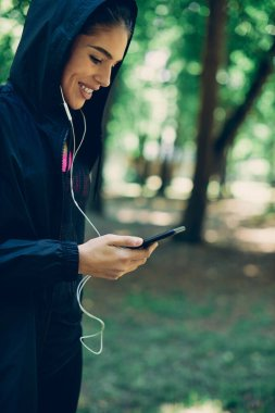 Young attractive caucasian sportswoman putting earphones and choosing music for running in nature.