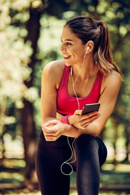 Young attractive caucasian female runner taking a break after running and using smart phone.