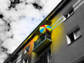 Colorful umbrella on the grey building background - the symbol of optimism and good life attitude