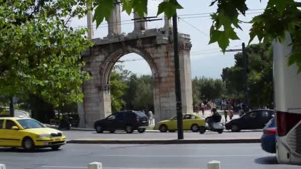 Atény, Řecko-duben 26, 2019.Auta projíždějící před Chrámem olympijského Dia za slunečného dne. Turisté jsou na návštěvě webu.