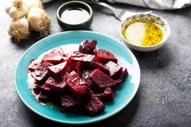 Beetroot salad with garlic and olive oil sauce in dish on dark background.