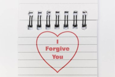 Text I Forgive You and a heart written in red on white paper