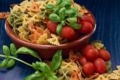 Schleife Nudeln, helle natürliche Farben, Basilikum grüne und rote Tomaten, mit blauen Szene